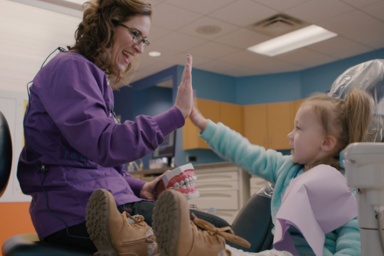Dentist High Fiving Young Patient